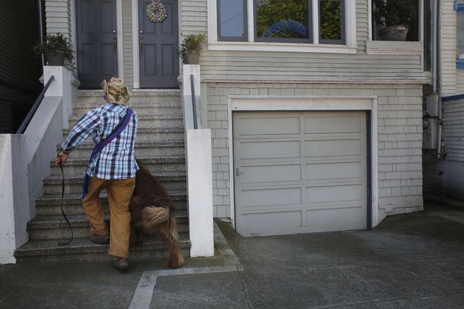 After a walks at Fort Funston, Wild Bill Peacock delivers a dog to its home in San Francisco, Calif. Photo: Mike Kepka, The Chronicle