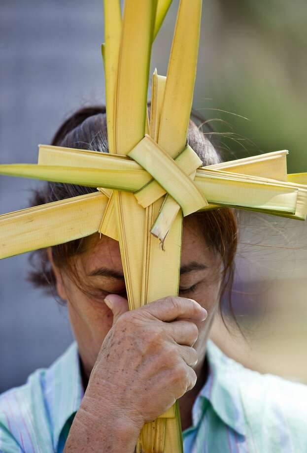 A woman holds palm fronds made into the shape of a cross during a Palm Sunday celebration outside the Metropolitan Cathedral in Managua, Nicaragua, Sunday, April 13, 2014. For Christians, Palm Sunday marks Jesus Christ's entrance into Jerusalem, when his followers laid palm branches in his path, prior to his crucifixion. (AP Photo/Esteban Felix) Photo: Esteban Felix, Associated Press