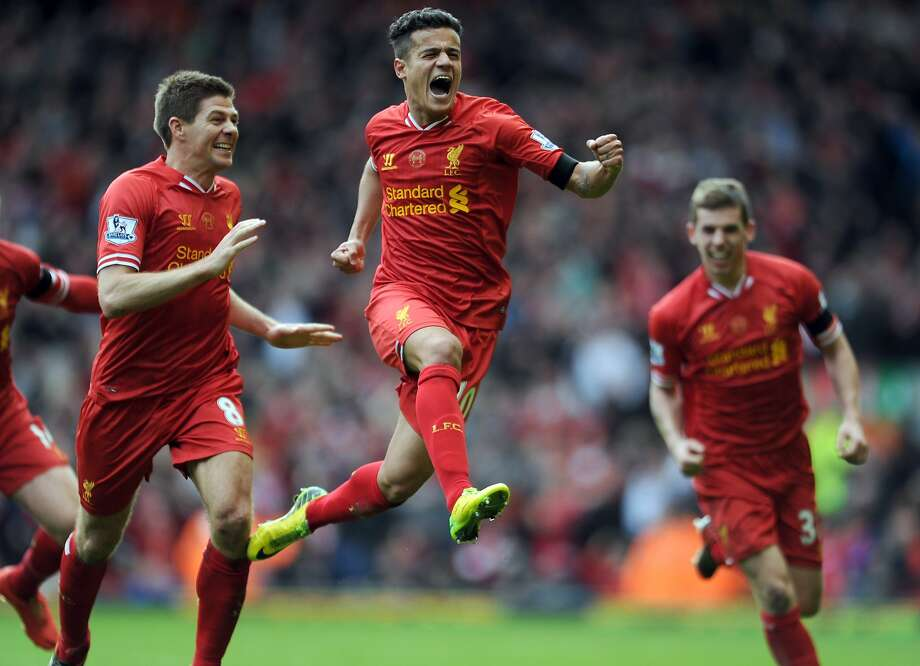 Liverpool's Philippe Coutinho, centre, celebrates with teammate Steven Gerrard, left, after he scored the third goal of the game for his side during their English Premier League soccer match against Manchester City at Anfield in Liverpool, England, Sunday April. 13, 2014. (AP Photo/Clint Hughes) Photo: Clint Hughes, Associated Press