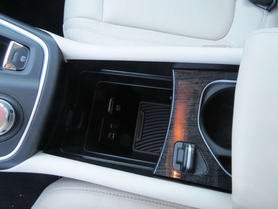 The cup holder section slides back to reveal a large cubby with 12-volt socket for a cell phone charger cord.
