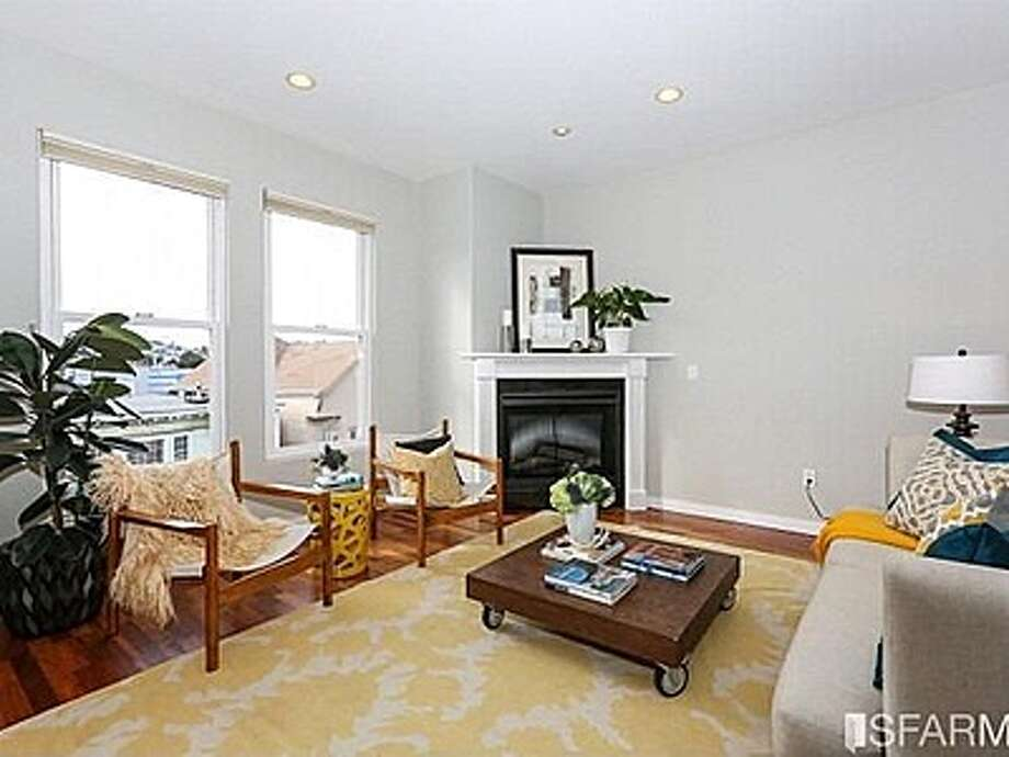 The living room has an electric fireplace and huge windows. Photo: MLS