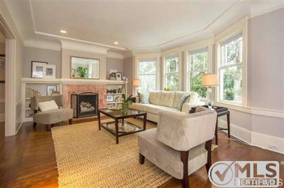 The living room has a wood-burning fireplace and the bay windows look out onto the Panhandle. Photo: MLS