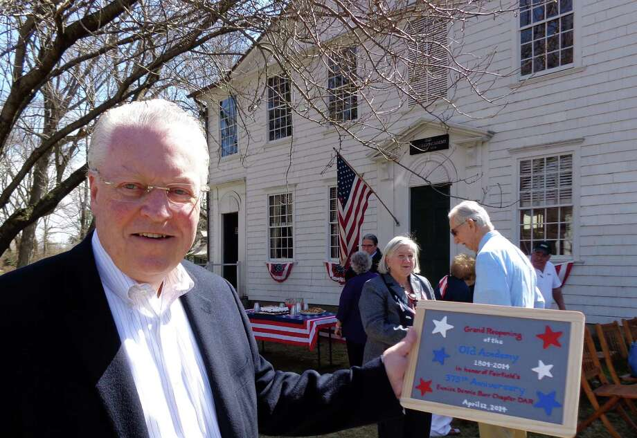 First Selectman Michael Tetreau holds a slate -- the early-19th-century version of a tablet computer in schools -- that he was given Saturday by the Eunice Dennie Burr Chapter of the Daughters of American Revolution during a re-dedication ceremony of the Old Academy on Town Hall Green. Photo: Meg Barone / Fairfield Citizen