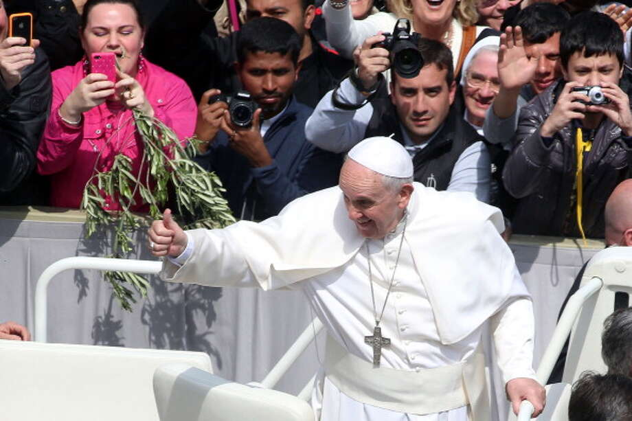 Pope Francis greets the faithful as he attends Palm Sunday Mass at St. Peter's Square on April 13, 2014 in Vatican City, Vatican. Palm Sunday, which is the sixth Sunday of Lent, marks the official beginning of Holy Week during which Christians recall the passion and death of Christ. Photo: Franco Origlia, Getty Images / 2014 Franco Origlia