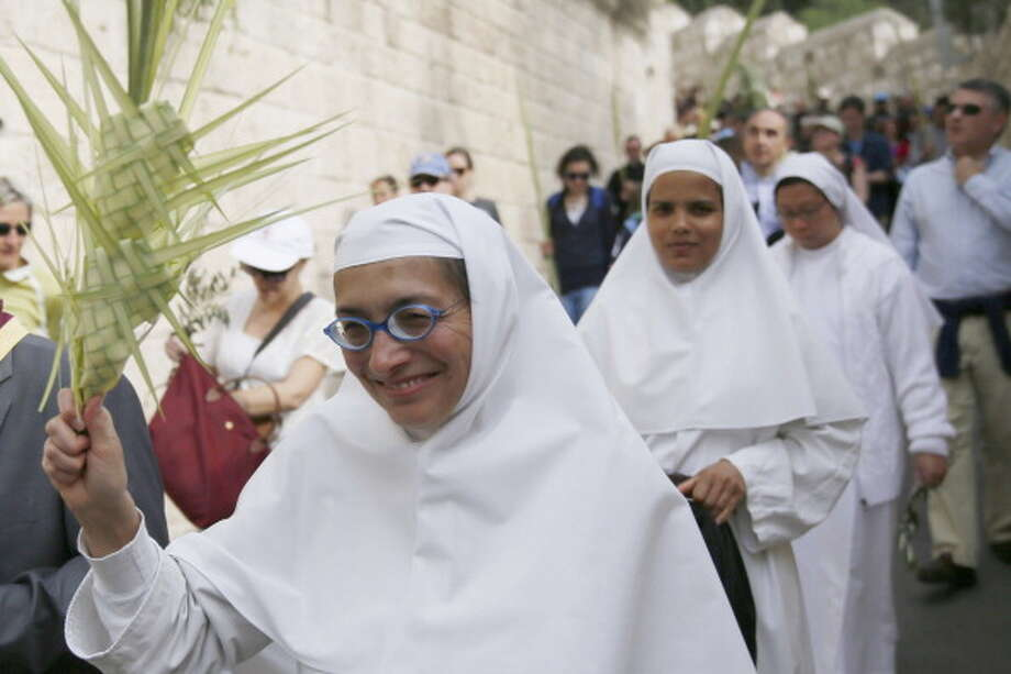 Catholic nuns take part in the traditional Palm Sunday procession from Mt. Olives to Jerusalem's Old City on April 13, 2014. The ceremony is a landmark in the Christian calendar, marking the triumphant return of Christ to Jerusalem the week before his death, when a cheering crowd greeted him waving palm leaves. Palm Sunday marks the start of the most solemn week in the Christian calendar. Photo: GALI TIBBON, AFP/Getty Images / 2014 AFP