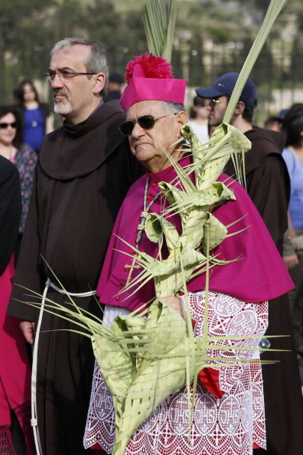 The head of the Roman Catholic Church in the Holy Land, the Latin Patriarch of Jerusalem Fuad Twal, carries a palm branch during the traditional Palm Sunday procession from Mt. Olives to Jerusalem's Old City on April  13, 2014. The ceremony is a landmark in the Christian calendar, marking the triumphant return of Christ to Jerusalem the week before his death, when a cheering crowd greeted him waving palm leaves. Palm Sunday marks the start of the most solemn week in the Christian calendar. Photo: GALI TIBBON, AFP/Getty Images / 2014 AFP
