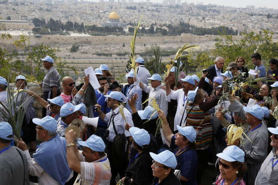 Pilgrims take part in the traditional Palm Sunday procession from Mt. Olives to Jerusalem's Old City on April  13, 2014. The ceremony is a landmark in the Christian calendar, marking the triumphant return of Christ to Jerusalem the week before his death, when a cheering crowd greeted him waving palm leaves. Palm Sunday marks the start of the most solemn week in the Christian calendar. Photo: GALI TIBBON, AFP/Getty Images / 2014 AFP