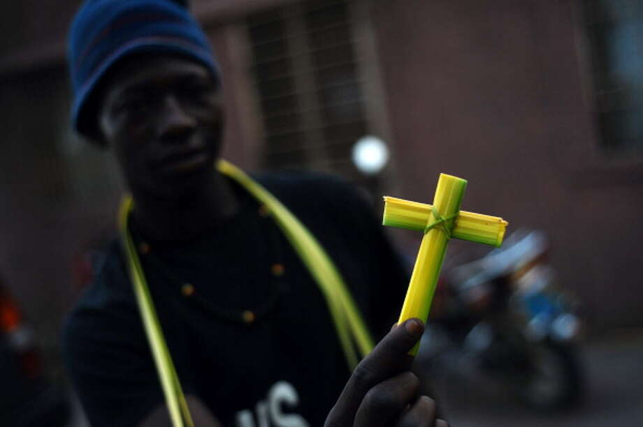"A Catholic faithful holds a cross made from palm leaves near St. Pierre Church in Port-au-Prince, on April 13, 2014. Palm Sunday is celebrated by Christians on the triumphal entry of Jesus Christ into Jerusalem, the week before his death and resurrection. For many Christian churches, Palm Sunday, often referred to as ""Passion Sunday,"" marks the beginning of Holy Week, which concludes on Easter Sunday. Photo: HECTOR RETAMAL, AFP/Getty Images / 2014 AFP"