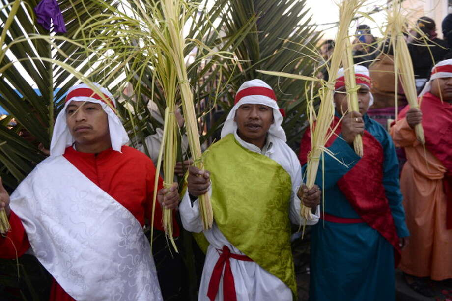 Catholic faithful take part in the Palm Sunday procession on April 13, 2013 in San Pedro Sacatepequez, 30 km west of Guatemala City. Palm Sunday marks the start of the most solemn week is the Roman Catholic calendar, marking the triumphant return of Christ to Jerusalem the week before his death, when a cheering crowd greeted him waving palm leaves. Photo: JOHAN ORDONEZ, AFP/Getty Images / 2014 AFP