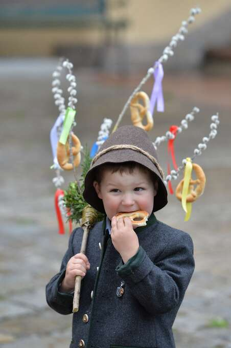 "The three years old Thomas Haitzmann eats a ""Palmbrezeln"" after a Palm Sunday procession in Lofer, Austrian province of Salzburg, Sunday, April 13, 2014. Palm Sunday opens the Holy Week which ends with Easter Sunday, the most important Christian holiday. Photo: Kerstin Joensson, Associated Press"