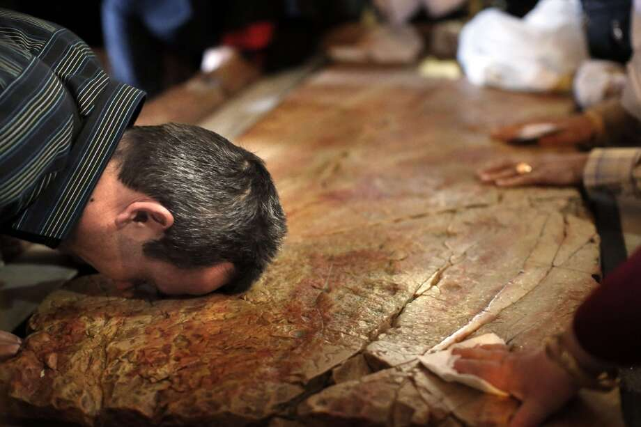 A Christian pilgrim prays on the Stone of the Anointing inside the Church of the Holy Sepulchre during the Palm Sunday procession in Jerusalem's Old City on April 13, 2014. The ceremony is a landmark in the Christian calendar, marking the triumphant return of Christ to Jerusalem the week before his death, when a cheering crowd greeted him waving palm leaves. Photo: THOMAS COEX, AFP/Getty Images
