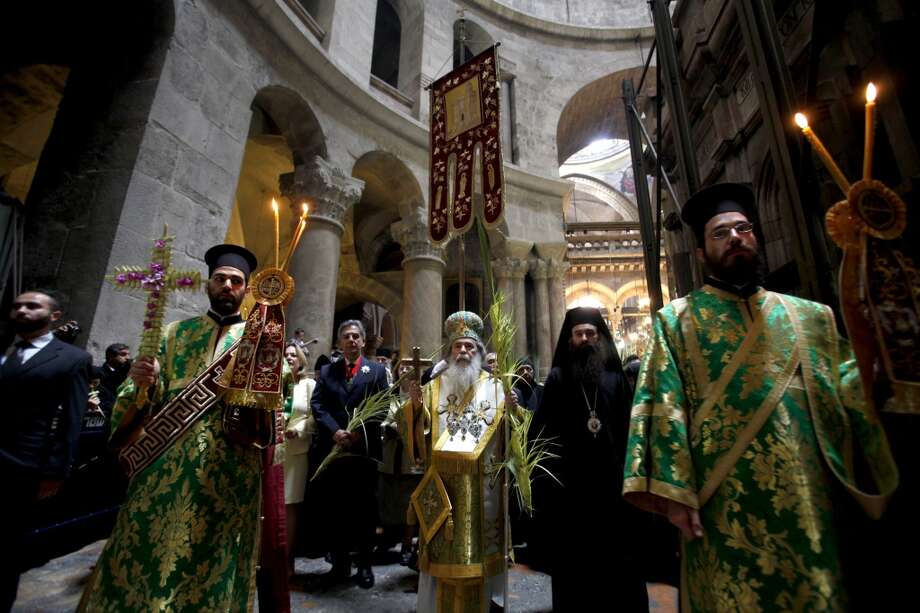 Greek Orthodox Patriarch of Jerusalem Theophilos III holds a cross and palm branches as he circles the aedicule during the Palm Sunday Easter procession at the Church of the Holy Sepulchre in Jerusalem's Old City on April 13, 2014. The ceremony is a landmark in the Christian calendar, marking the triumphant return of Christ to Jerusalem the week before his death, when a cheering crowd greeted him waving palm leaves. Photo: GALI TIBBON, AFP/Getty Images