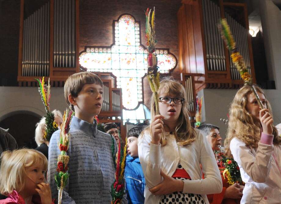 Children hold hand made palms during a Palm Sunday Mass in a church in Warsaw, Poland, Sunday, April 13, 2014.  Palm Sunday opens the Holy Week that ends with Easter Sunday, the most important Catholic holiday. Photo: Alik Keplicz, Associated Press