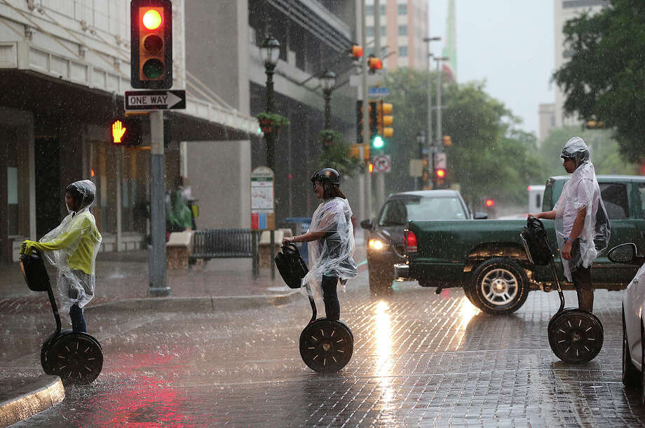 A segway tour gets caught in the rain as a cold front blows through downtown San Antonio, Monday, April 14, 2014. After a warm weekend, the front is expected to drop the temperatures into the 40's and 50's. Photo: Jerry Lara, San Antonio Express-News / ©2014 San Antonio Express-News