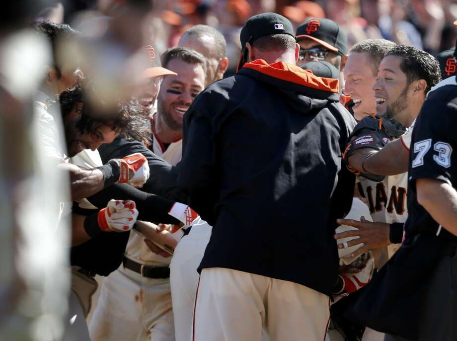 Brandon Crawford (not seen) is mobbed by teammates after his homer in the 10th inning. The San Francisco Giants defeated the Colorado Rockies 5-4 in ten innings Sunday April 13, 2014 at AT&T park. Photo: The Chronicle