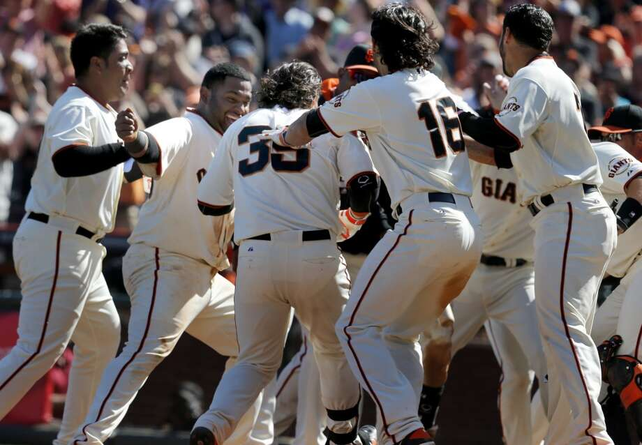 Brandon Crawford (35) is mobbed by teammates after his game winning homer in the tenth inning. The San Francisco Giants defeated the Colorado Rockies 5-4 in ten innings Sunday April 13, 2014 at AT&T park. Photo: The Chronicle