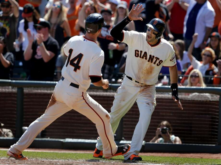 Michael Morse (right) and Brandon Hicks (14) arrived at home plate after a hit by Angel Pagan in the fifth inning. The San Francisco Giants defeated the Colorado Rockies 5-4 in ten innings Sunday April 13, 2014 at AT&T park. Photo: The Chronicle