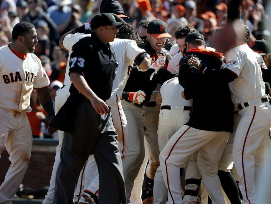 Brandon Crawford is mobbed by teammates after his home run. The San Francisco Giants defeated the Colorado Rockies 5-4 in ten innings Sunday April 13, 2014 at AT&T park. Photo: The Chronicle