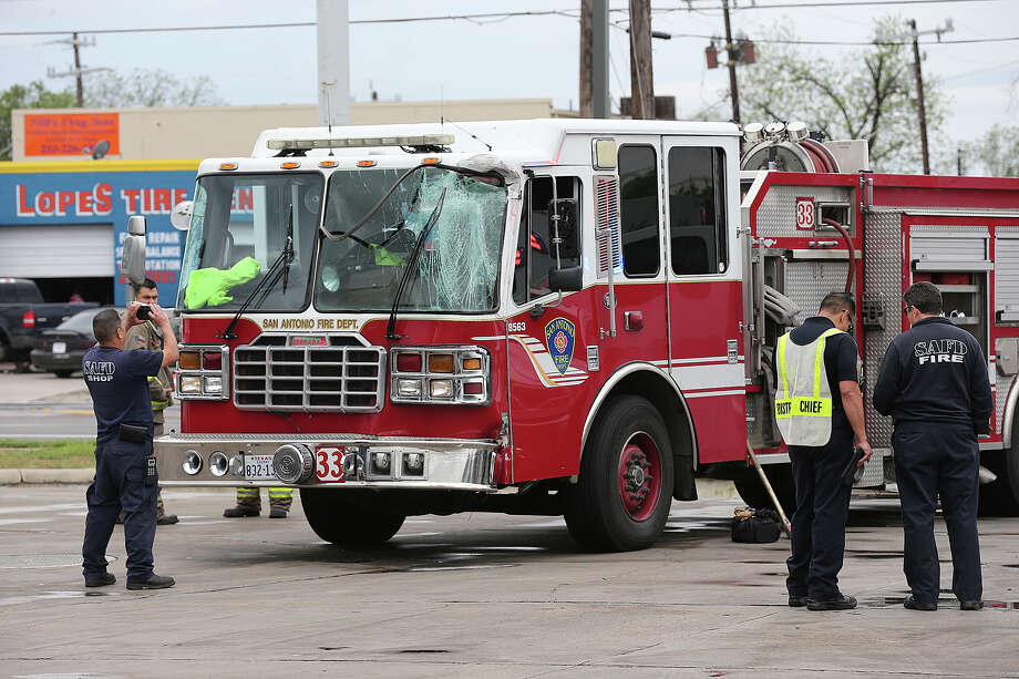 Emergency personnel work the scene of an vehicle accident involving two San Antonio Fire Department vehicles at the 2200 block of South Zarzamora, Monday, April 14, 2014. A male was transported from the scene by EMS. Photo: Jerry Lara, San Antonio Express-News / ©2014 San Antonio Express-News
