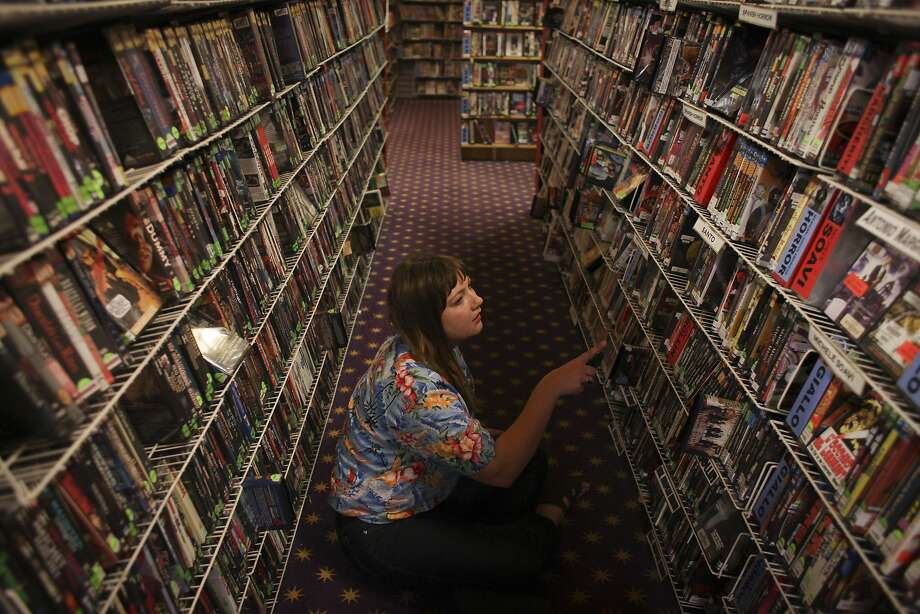 Maya Falkenberg looks around for a film to rent on the second floor of Le Video in San Francisco's Sunset District. Photo: Sam Wolson, Special To The Chronicle