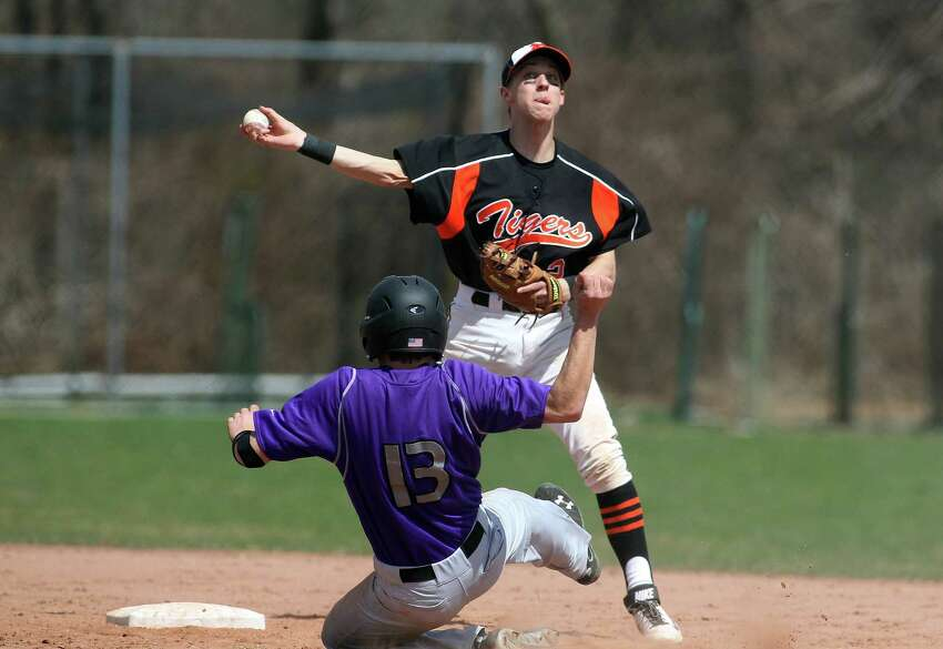 Ridgefield High School second baseman Liam Smith (# 2) forces out Westhill runner Mike Rossi (#13) on the front end of a double play ball during FCIAC baseball in Stamford, Conn. on Monday, April 14, 2014. Westhill won the tightly fought game, 5-4.