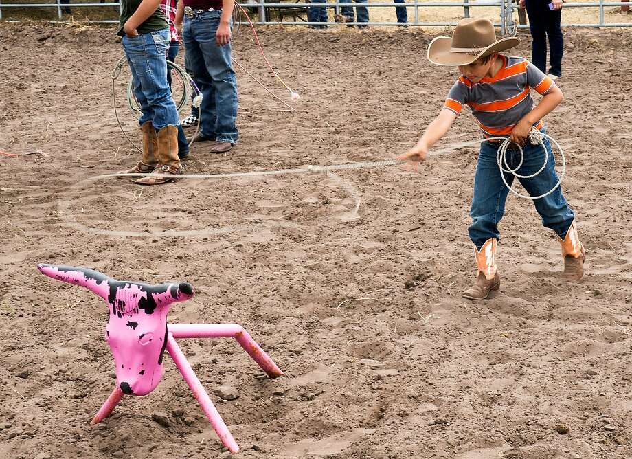 'Calf' roping, Texas-style: A young boy shows off his lassoing technique in the Kids Dummy 