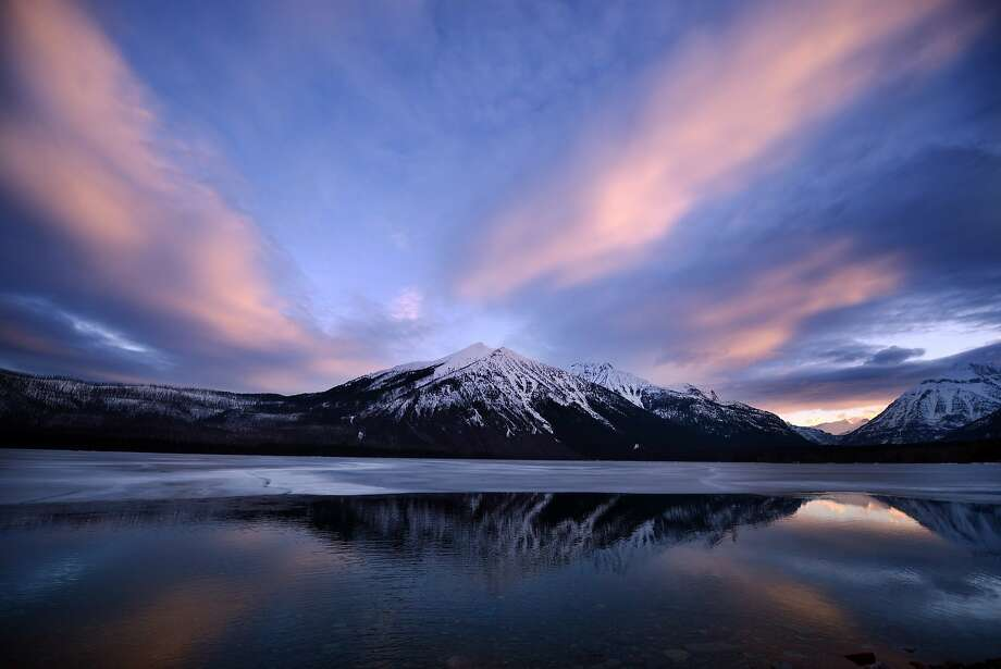Melting in Montana: Glassy Lake McDonald, its ice slowly disappearing, reflects the sunrise on a chilly morning in Glacier National Park, 