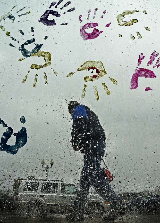 Bundled in his raincoat, Robert Scheinoha hurries to catch the bus as he walks past a 