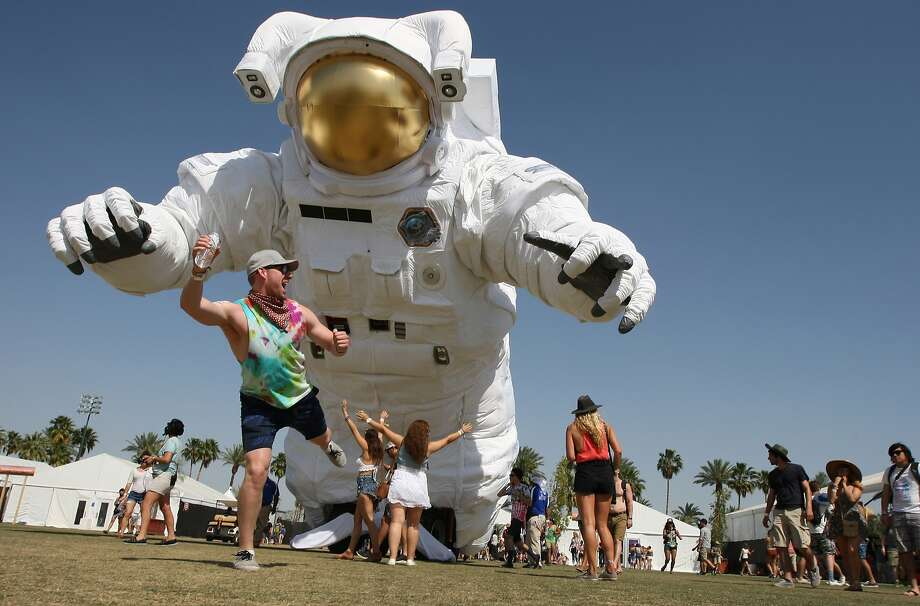 "Run for your lives!A concert-goer feigns panic in front of the towering inflated artwork ""Escape Velocity"" at the Coachella Valley Music & Arts Festival in Indio, Calif. Photo: David McNew, AFP/Getty Images"