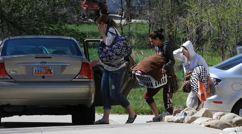 People carry belongings from the house where seven infant bodies were discovered. Photo: Rick Bowmer, Associated Press