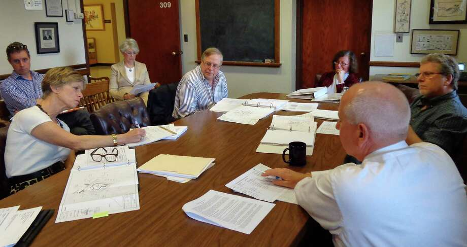 Selectman Helen Garten, at head of table, and First Selectman Jim Marpe, foreground, discuss isses facing the new Kemper-Gunn House Advisory Group, which is planning for the downtown relocation of the historic house. Photo: Meg Barone / Westport News