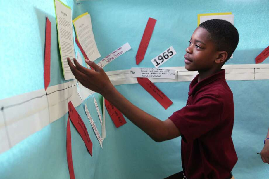 Classical Studies Academy student Jaden McLellan gives a tour of a sixth grade project on African American Olympians on Monday, April 7, 2014 in Bridgeport, Conn. Photo: BK Angeletti, B.K. Angeletti / Connecticut Post freelance B.K. Angeletti