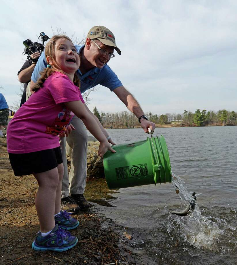 Makayla Kepner, 8, of Watervliet is excited to help Greg Kozlowski from the state Department of Environmental Conservation with the stocking of Rensselaer Lake Monday morning, April 14, 2014, at Six Mile Waterworks in Albany, N.Y. (Skip Dickstein / Times Union) Photo: SKIP DICKSTEIN / 00026478A