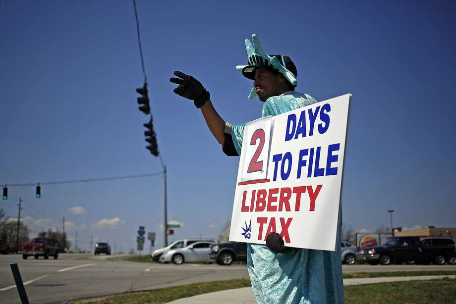 Steven Flagg waves to motorists while holding a sign for a nearby Liberty Tax Service franchise location in Louisville, Ky. Tuesday is the deadline to submit tax returns. Photo: Luke Sharrett, Bloomberg