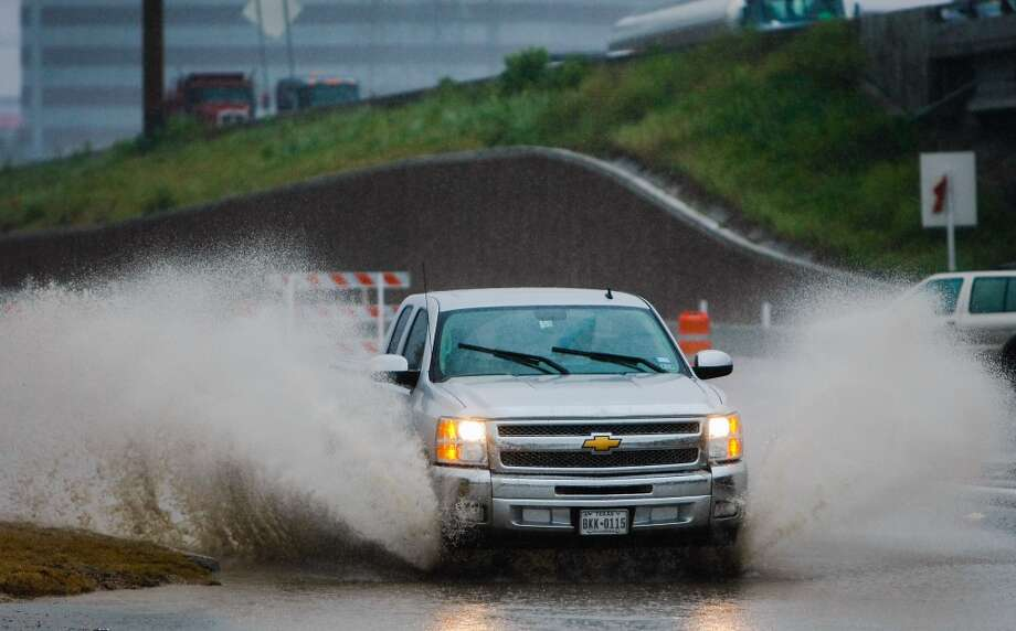 Rain pours as a truck makes its way through a standing water along W. 34th Street, Monday, April 14, 2014, in Houston. (Cody Duty / Houston Chronicle) Photo: Cody Duty, Houston Chronicle