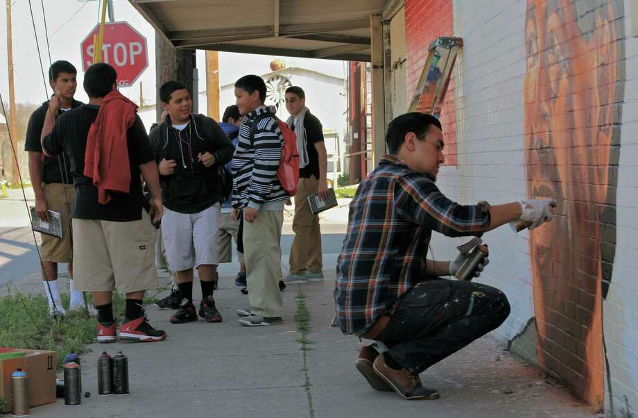 ABOVE: A group of young people gather as San Antonio artist Christopher Montoya, 21, puts the finishing touches on his giant mural honoring Cesar Chavez, the late labor organizer.                    AT LEFT: The colorful mural honoring Chavez is at the corner of South Flores and Pruitt. Montoya is a graduate of Brackenridge High. Photo: Courtesy Photos