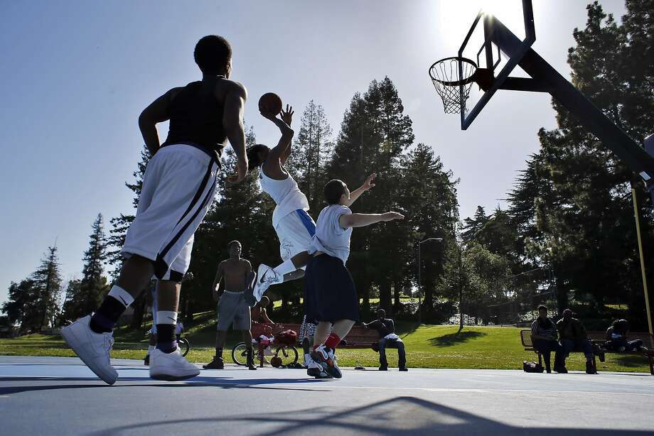 Raunte Colly shoots a basket during a game with friends at Brookdale Park in Oakland, which may begin seeking donors to pay for maintaining public parks and, in return, letting them take credit for their support. Photo: Carlos Avila Gonzalez, The Chronicle