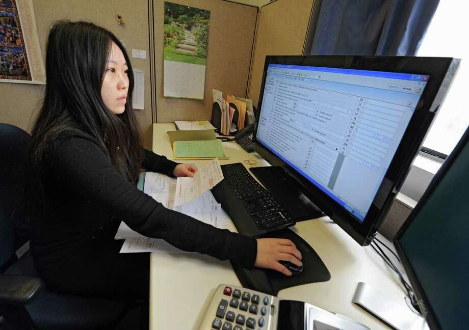 Employee Ying Xu, a graduate of RPI, works on filing taxes  for clients at Jordan & Savoy certified public accountants office on Monday, April 14, 2014 in Troy, N.Y. The dealing is tomorrow. (Lori Van Buren / Times Union) Photo: Lori Van Buren / 00026490A