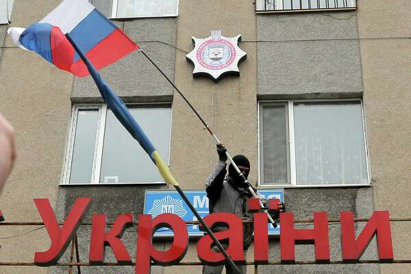 """A pro-Russian man places a Russian flag over a police station during its mass storming in the eastern Ukrainian town of Horlivka on Monday, April 14, 2014.  The text reads: Ukrainian police station in Horlivka"""". Several government buildings has fallen to mobs of Moscow loyalists in recent days as unrest spreads across the east of the country.  (AP Photo/Efrem Lukatsky)"""