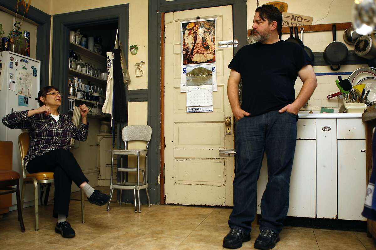 Patricia Kerman (left) talks in the kitchen with her roommate Tom Rapp in the kitchen of their apartment in San Francisco, Calif., on Sunday, February 2, 2014. They were served an Ellis Act eviction notice last August.