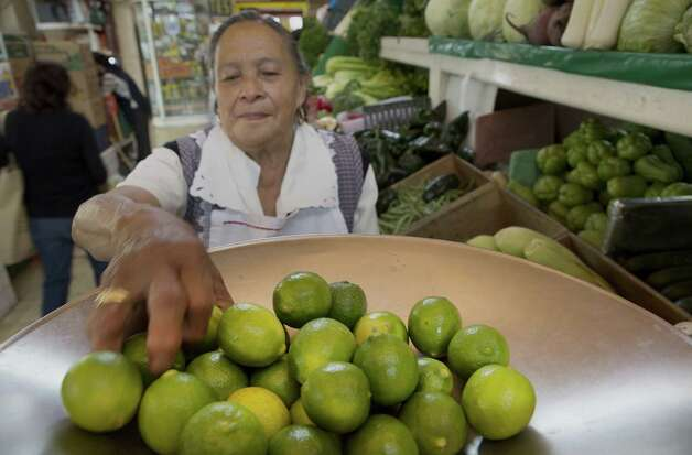 Lilia Olivares, owner of a small stand of fruits and vegetables, weighs limes at a market in Mexico City. Farmers in Michoacán state are accused of fixing prices on the fruit. Photo: Susana Gonzalez / Bloomberg / © 2014 Bloomberg Finance LP