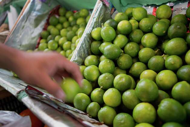 A market employee picks limes for a customer at the Michoacan market in the Condesa neighborhood of Mexico City, Mexico, on Wednesday, April 2, 2014. Lime growers in the Mexican state of Michoacan have banded together to both set prices of the fruit they sell to packing companies and control supply, spurring inflation that's been above the central bank's target range for the last two months. Photographer: Susana Gonzalez/Bloomberg Photo: Bloomberg / © 2014 Bloomberg Finance LP