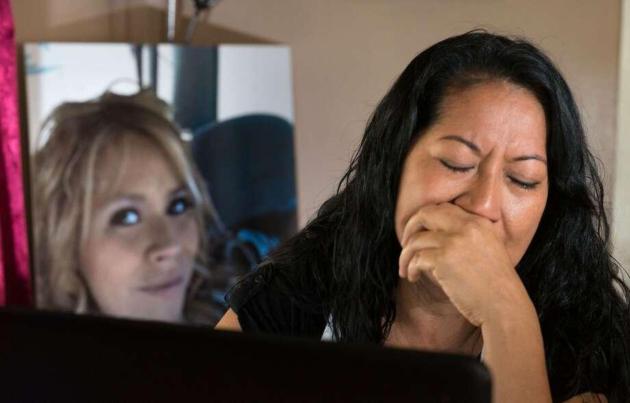 A portrait of murder victim Martha Anaya, left, is seen on a table as her mother Herlinda Salcedo cries in Santa Ana. Photo: Eugene Garcia,, Associated Press