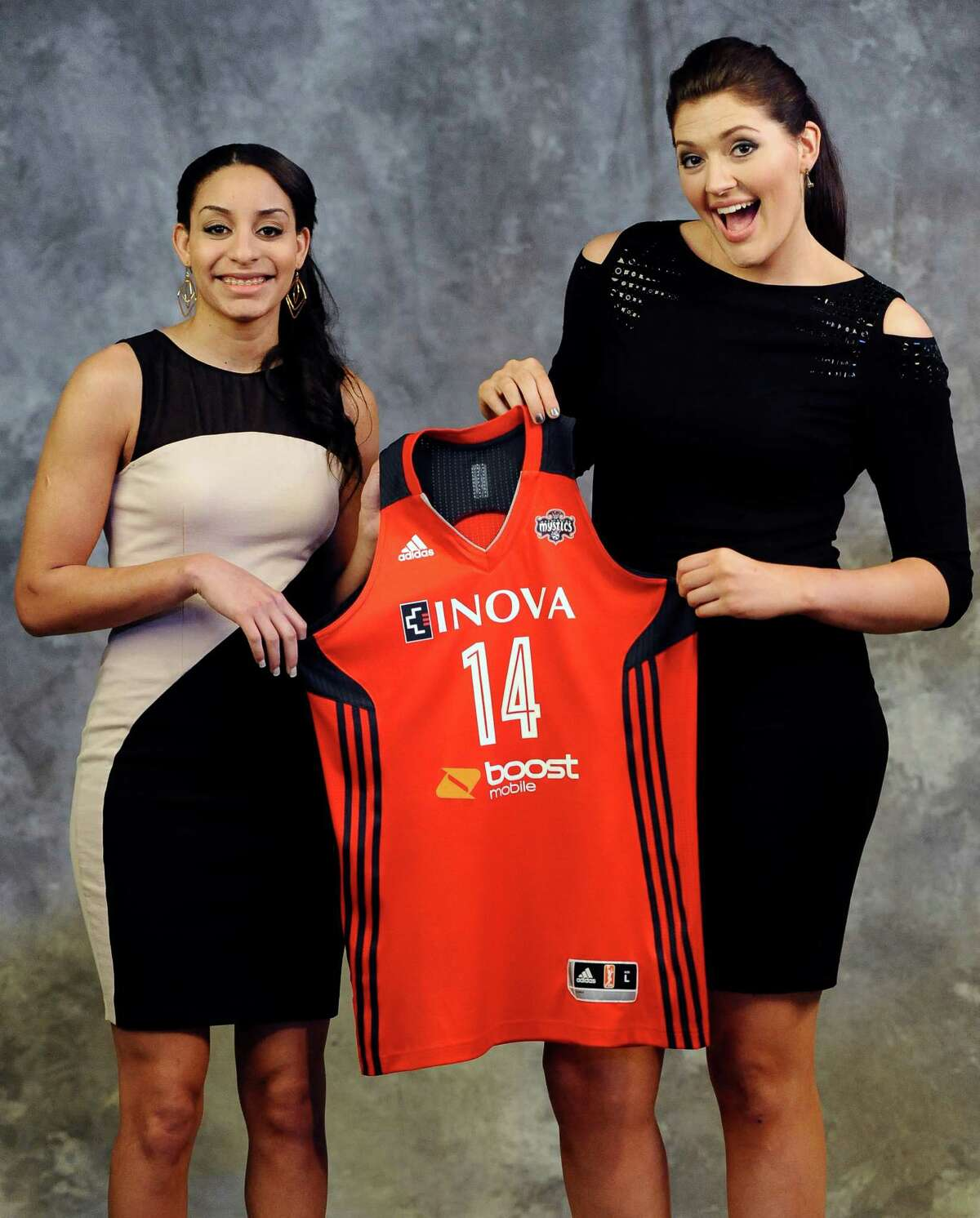 Connecticut's Bria Hartley, left, and Stefanie Dolson, hold up a Washington Mystics jersey after Hartley was traded from the Seattle Storm to the Washington Mystics to play with Dolson in the WNBA basketball draft in, Monday, April 14, 2014, in Uncasville, Conn.