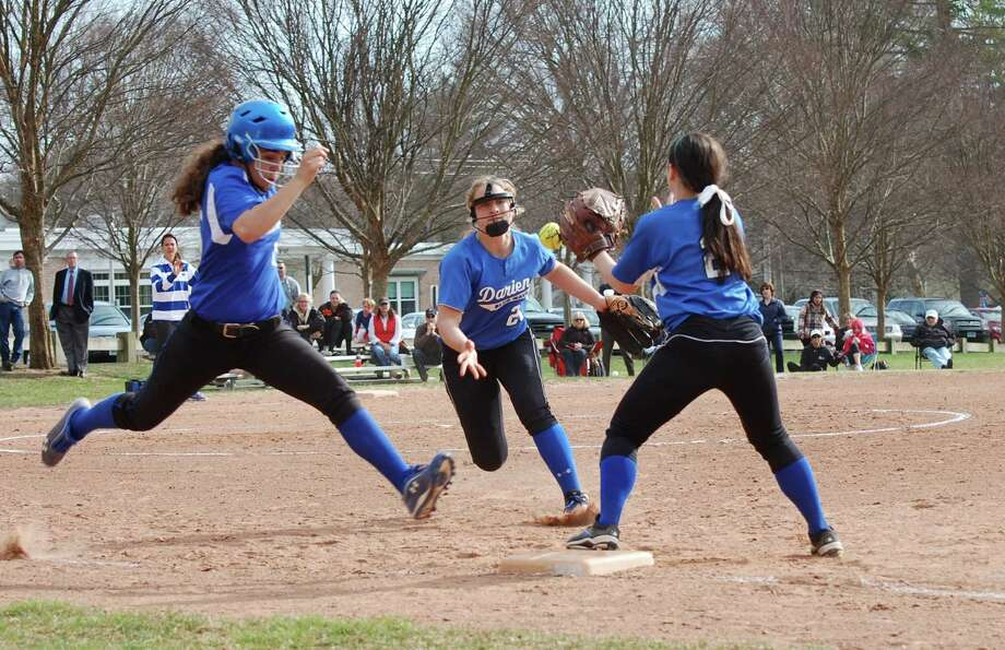 Darien's Erika Osherow flips the ball to Kelly Vedola to retire Ludlowe's Nene Capeles during a regular season game on Monday, April 14. Photo: Dave Crandall / Darien News freelance