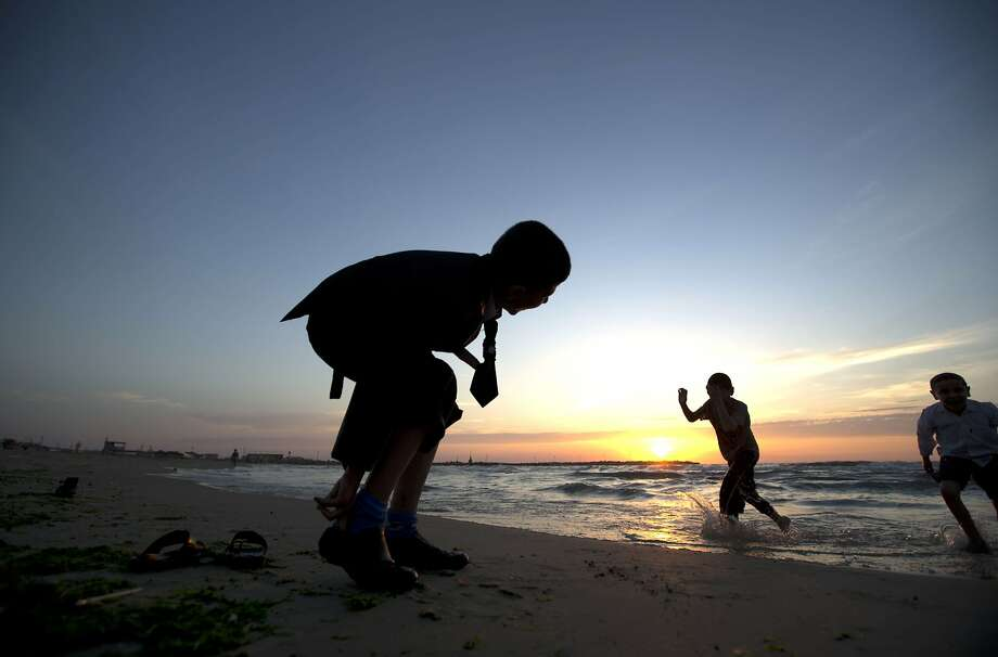 Palestinian children play on the beach in Gaza City on April 14, 2014. TOPSHOTS/AFP PHOTO/MOHAMMED ABEDMOHAMMED ABED/AFP/Getty Images Photo: Mohammed Abed, AFP/Getty Images