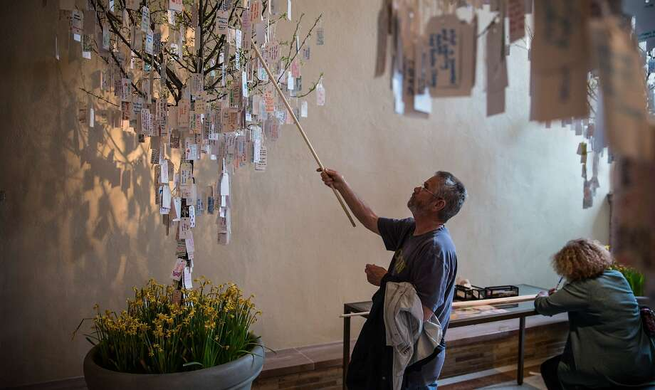 "BOSTON, MA - APRIL 14:  Joe Leary, from West Barnstable, Massachuestts, hangs a hand-written message he wrote on a tree hung with messages inside a display titled, ""Dear Boston: Messages from the Marathon Memorial"" in the Boston Public Library to commemorate the 2013 Boston Maraton bombings, on April 14, 2014 in Boston, Massachusetts. Last year, two pressure cooker bombs killed three and injured an estimated 264 others during the Boston marathon, on April 15, 2013.  (Photo by Andrew Burton/Getty Images) Photo: Andrew Burton, Getty Images"