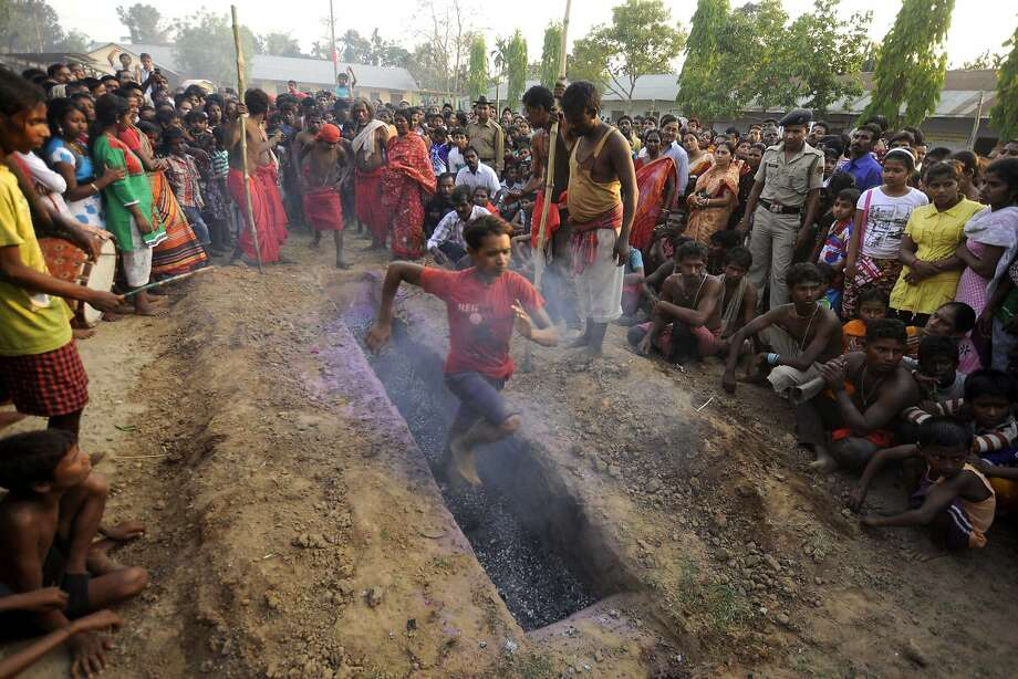 A Hindu devotee runs over smouldering charcoal during the ritual of Shiva Gajan at Pratapgarh village in Agartala, the capital of northeastern Indian state of Tripura, on April 14, 2014. Devotees believe that by enduring the pain, Shiva, the Hindu god of destruction, will grant their prayers. Thousands took part in the month-long festival which culminates with the worship of Shiva on the auspicious day of Chaitra Sankranti, the last day of the Bengali calendar year. TOPSHOTS/AFP PHOTO/ ARINDAM DEYARINDAM DEY/AFP/Getty Images Photo: Arindam Dey, AFP/Getty Images