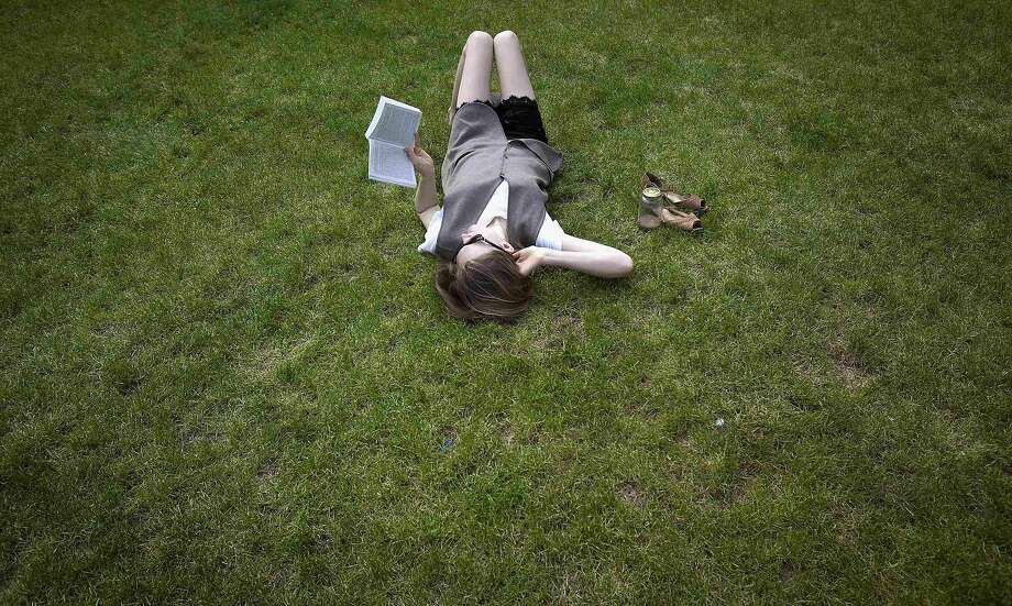 A woman lies in the grass while reading a book, at Columbia University in New York, April 14, 2014. The temperature reached an unseasonably high 77 Fahrenheit (25 Celsius). REUTERS/Carlo Allegri (UNITED STATES - Tags: SOCIETY ENVIRONMENT EDUCATION TPX IMAGES OF THE DAY) Photo: Carlo Allegri, Reuters