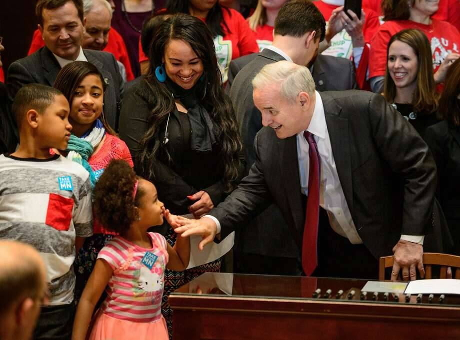 Minnesota Gov. Mark Dayton high-fived Ashia Rhodes, whose mother, Jacquita Berens, who works three jobs and will benefit from the minimum wage increase.Gov. Dayton signed the minimum wage bill into law at a public bill signing ceremony in the Minnesota State Capitol Rotunda in St. Paul, Minn., Monday, April 14, 2014. The bill, which passed by the Legislature last week, will increase Minnesota's minimum wage to $9.50 per hour, and index it to inflation. (Glen Stubbe/Minneapolis Star Tribune/MCT) Photo: Glen Stubbe, McClatchy-Tribune News Service